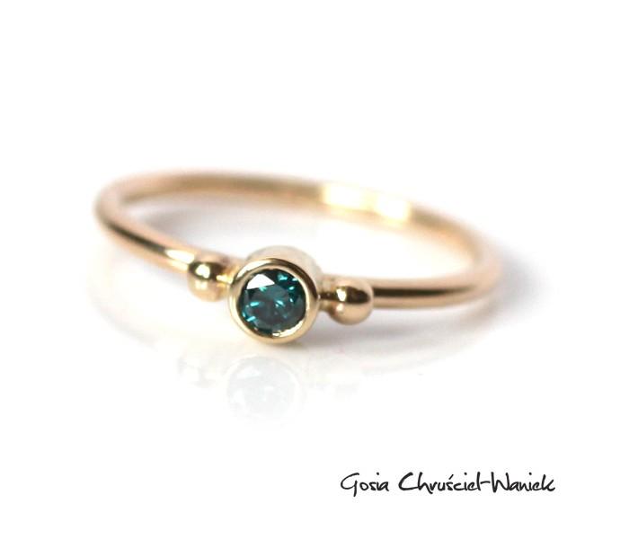 Złoty pierścionek z niebieskim brylantem